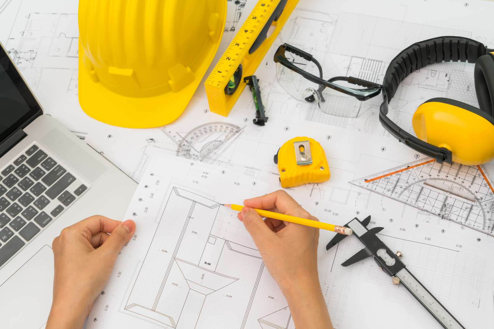Hand over Construction plans with yellow helmet and drawing tools on blueprints